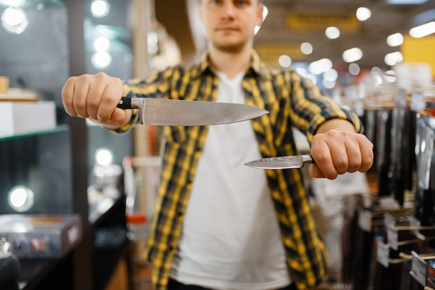 Młody Człowiek Trzyma Noże Kuchenne W Sklepie Agd. Mężczyzna Kupuje Towary Domowe Na Rynku, Facet W Sklepie Z Zaopatrzeniem W Naczynia Kuchenne Premium Zdjęcia