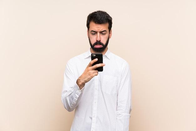 Młody Człowiek Trzyma Telefon Komórkowy Z Smutnym I Przygnębionym Wyrażeniem Z Brodą Premium Zdjęcia