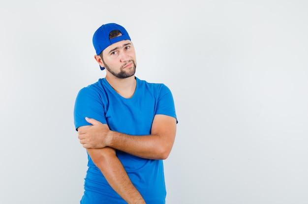 Młody Człowiek Trzymając Rękę Z Ręką W Niebieskiej Koszulce I Czapce I Patrząc Zamyślony Darmowe Zdjęcia