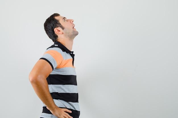 Młody Człowiek Trzymając Się Za Ręce Na Jego Talii, Patrząc W T-shirt I Wyglądając Na Znudzonego. Wolne Miejsce Na Tekst Darmowe Zdjęcia