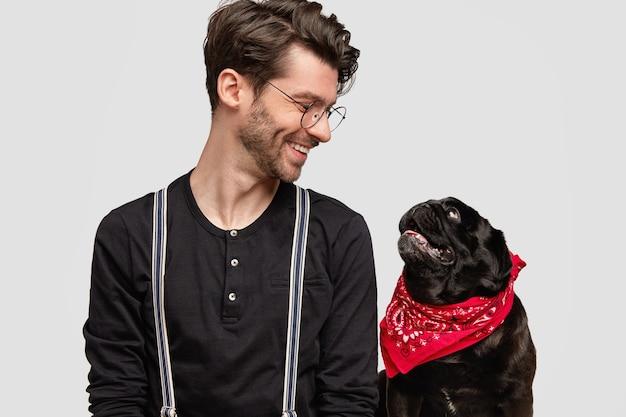 Młody Człowiek Ubrany W Czerwoną Chustkę I Czarną Koszulę I Jego Psa Darmowe Zdjęcia