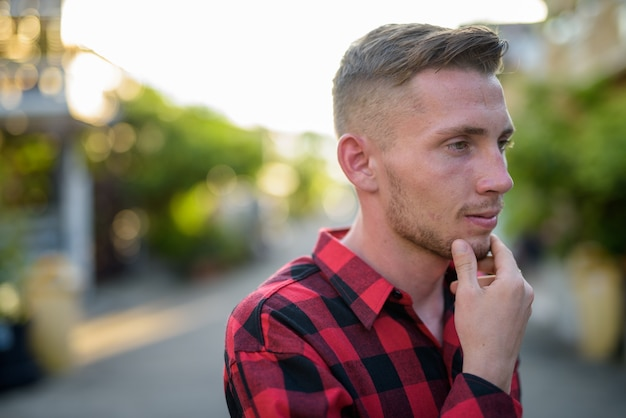 Młody Człowiek Ubrany W Czerwoną Kraciastą Koszulę Na Ulicach Na Zewnątrz Premium Zdjęcia