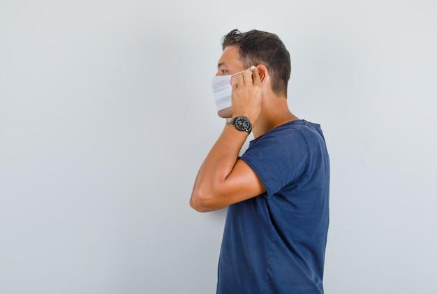 Młody Człowiek Ubrany W Maskę Medyczną W Ciemnoniebieskiej Koszulce. Darmowe Zdjęcia