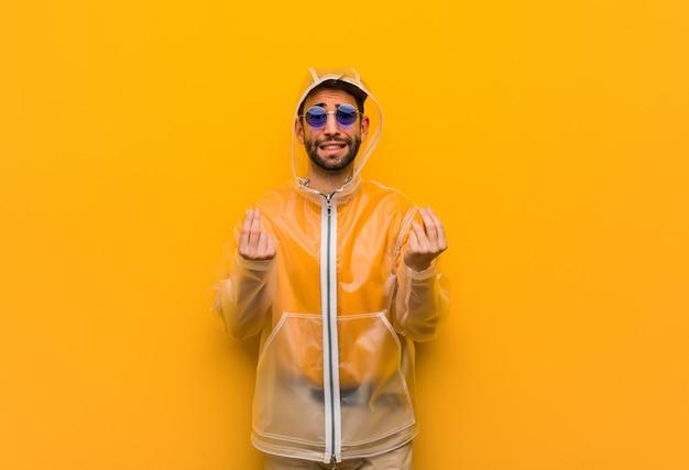 Młody Człowiek Ubrany W Płaszcz Przeciwdeszczowy Robi Gest Potrzeby Premium Zdjęcia