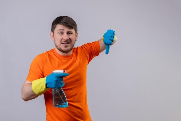 Młody Człowiek Ubrany W Pomarańczowy T-shirt I Rękawice Gumowe, Trzymając Spray Do Czyszczenia Ze Smutnym Wyrazem Twarzy Darmowe Zdjęcia