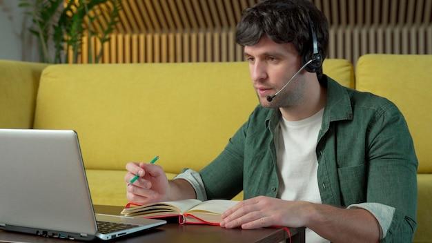 Młody Człowiek Ubrany W Słuchawki Siedzi Na żółtej Kanapie W Domu I Rozmawia Przez łącze Wideo Na Laptopie Premium Zdjęcia