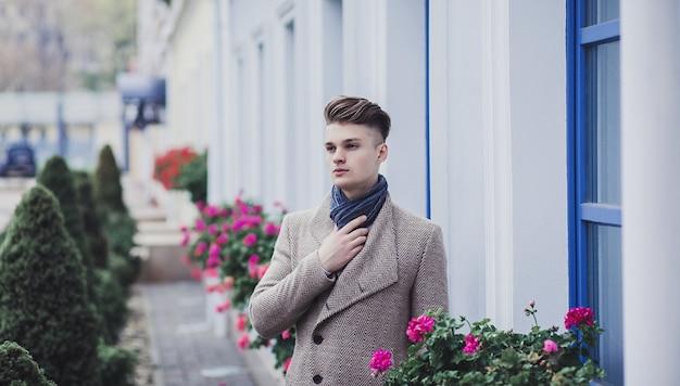 Młody Człowiek Ubrany W Ubranie Na Ulicy. Facet Z Nowoczesną Fryzurą I Płaszczem Premium Zdjęcia