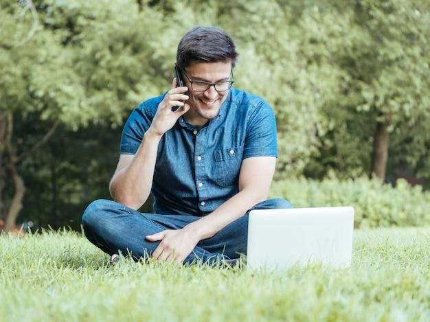 Młody Człowiek Używa Smartphone Podczas Gdy Siedzący Na Trawie Premium Zdjęcia
