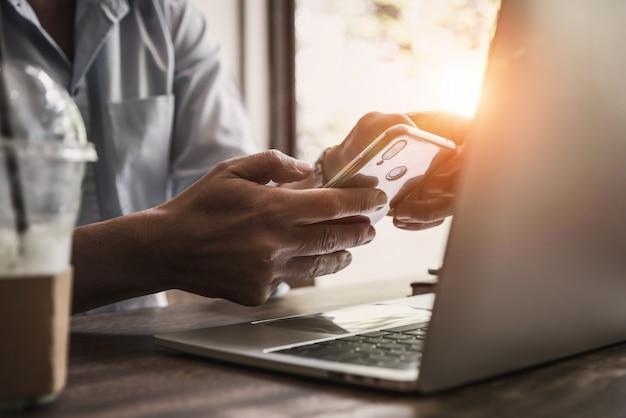 Młody Człowiek Używa Telefon Komórkowego W Sklep Z Kawą Premium Zdjęcia