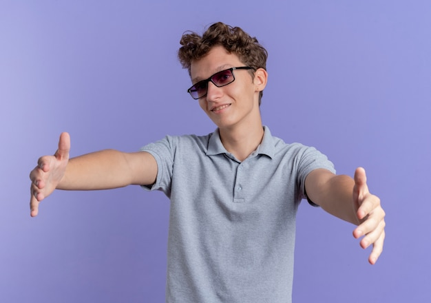 Młody Człowiek W Czarnych Okularach Na Sobie Szarą Koszulkę Polo Uśmiechnięty Przyjacielski Czyniąc Powitalny Gest Szeroko Otwierając Ręce Stojąc Na Niebieskiej ścianie Darmowe Zdjęcia