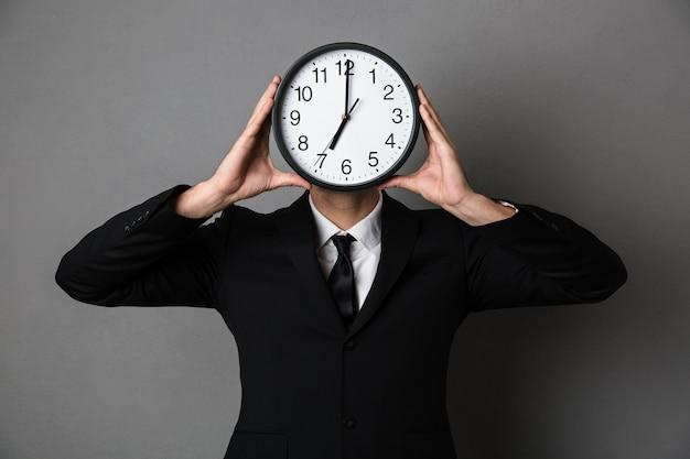 Młody Człowiek W Czarnym Garniturze Gospodarstwa Zegar Przed Jego Twarzą Darmowe Zdjęcia