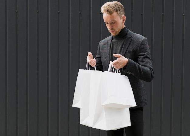Młody człowiek w czerni patrzeje w torba na zakupy Darmowe Zdjęcia