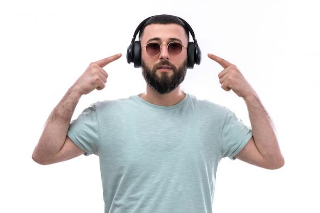 Młody Człowiek W Niebieską Koszulkę Z Brodą, Słuchanie Muzyki Przez Czarne Słuchawki Darmowe Zdjęcia