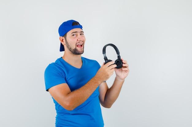 Młody Człowiek W Niebieskiej Koszulce I Czapce, Trzymając Słuchawki I Patrząc Optymistycznie Darmowe Zdjęcia