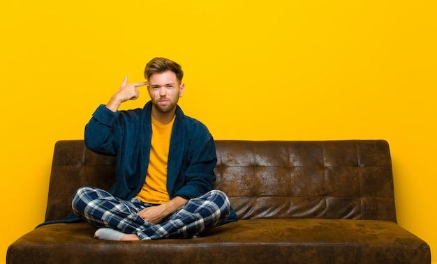Młody Człowiek W Piżamie Czuje Się Zdezorientowany I Zdziwiony, Pokazując, że Jesteś Szalony, Szalony Lub Oszalał Premium Zdjęcia