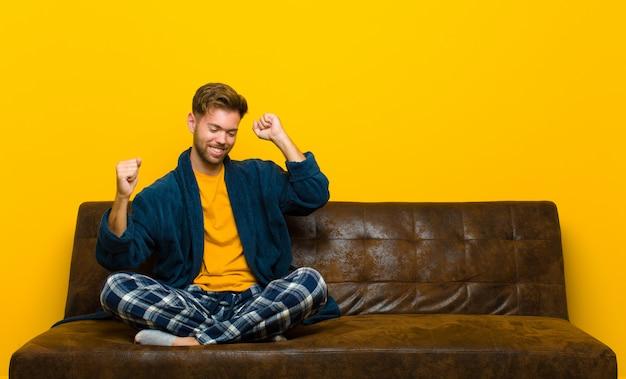 Młody człowiek w piżamie, uśmiechając się, czując się beztrosko, zrelaksowany i szczęśliwy, tańcząc i słuchając muzyki, dobrze się bawiąc na imprezie. siedzieć na kanapie Premium Zdjęcia