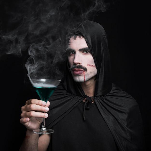 Młody człowiek w płaszcz z kapturem pozowanie w studio z napojami parze Darmowe Zdjęcia
