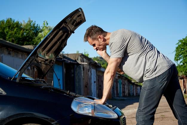 Młody człowiek w pobliżu samochodu z otwartym kapturem. Premium Zdjęcia