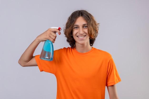 Młody Człowiek W Pomarańczowej Koszulce Gospodarstwa Spray Do Czyszczenia Patrząc Na Kamery Uśmiechnięty Wesoło Stojąc Na Białym Tle Darmowe Zdjęcia