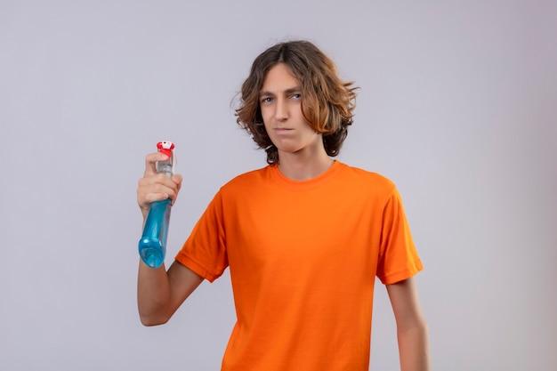 Młody Człowiek W Pomarańczowej Koszulce Gospodarstwa Spray Do Czyszczenia Patrząc Na Kamery Ze Smutnym Wyrazem Twarzy Stojącej Na Białym Tle Darmowe Zdjęcia