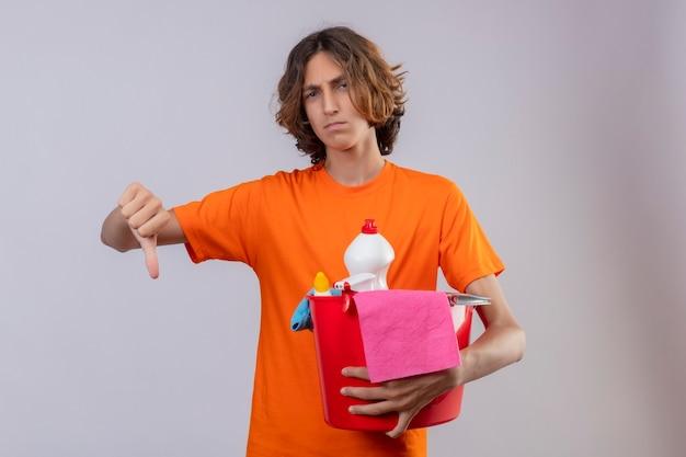 Młody Człowiek W Pomarańczowej Koszulce, Trzymając Wiadro Z Narzędziami Do Czyszczenia, Patrząc Na Kamery Niezadowolony, Pokazując Kciuk W Dół Stojący Na Białym Tle Darmowe Zdjęcia