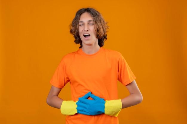 Młody Człowiek W Pomarańczowej Koszulce W Gumowych Rękawiczkach, śmiejąc Się, Dotykając Jego żołądka Stojącego Na żółtym Tle Darmowe Zdjęcia
