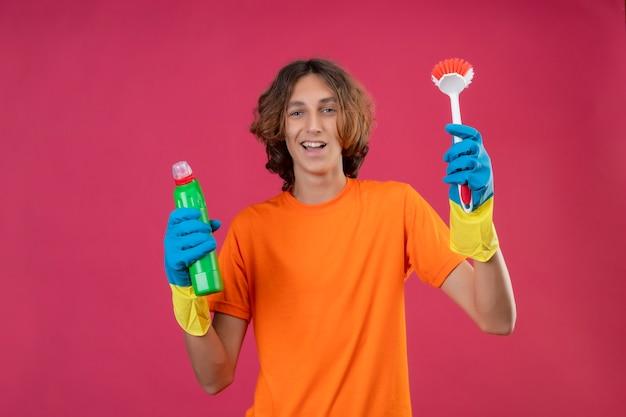 Młody Człowiek W Pomarańczowej Koszulce W Gumowych Rękawiczkach, Trzymając Butelkę środków Czyszczących I Szczoteczkę Do Szorowania, Patrząc Na Kamerę, Uśmiechnięty Wesoło Szczęśliwy I Pozytywny Stojący Nad Różowym Deseniem Darmowe Zdjęcia