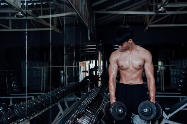 Młody człowiek w sportowej klasy ćwiczeń w siłowni Darmowe Zdjęcia