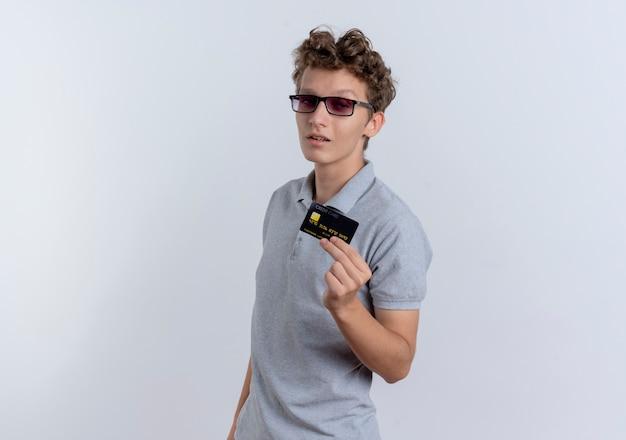Młody Człowiek W Szarej Koszulce Polo Pokazując Kartę Kredytową Pewnie Stojąc Na Białej ścianie Darmowe Zdjęcia