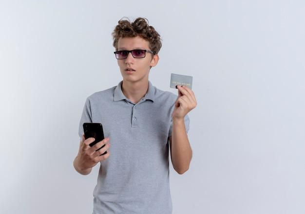 Młody Człowiek W Szarej Koszulce Polo Trzymając Smartfon Pokazując Kartę Kredytową Mylić Stojąc Na Białej ścianie Darmowe Zdjęcia
