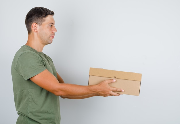 Młody Człowiek W Zielonej Armii T-shirt Dostarczający Karton. Darmowe Zdjęcia