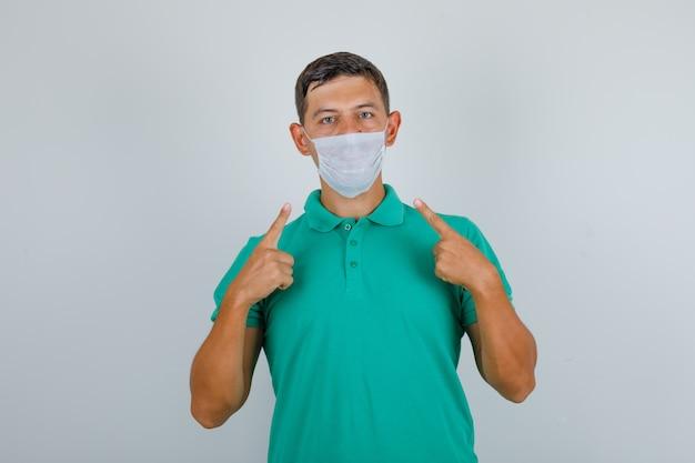 Młody Człowiek W Zielonej Koszulce Pokazano Jego Maskę Medyczną I Patrząc Uważnie, Widok Z Przodu. Darmowe Zdjęcia