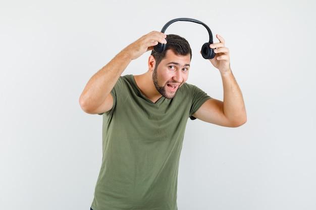 Młody Człowiek W Zielonej Koszulce Próbuje Nosić Słuchawki Darmowe Zdjęcia