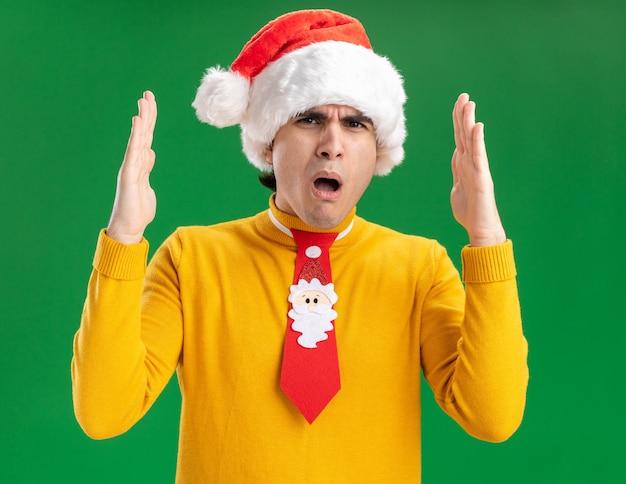 Młody Człowiek W żółtym Golfie I Czapce Mikołaja Z Zabawnym Krawatem Zdumiony Pokazujący Duży Gest Z Rękami, Symbol Miary Stojący Nad Zieloną ścianą Darmowe Zdjęcia
