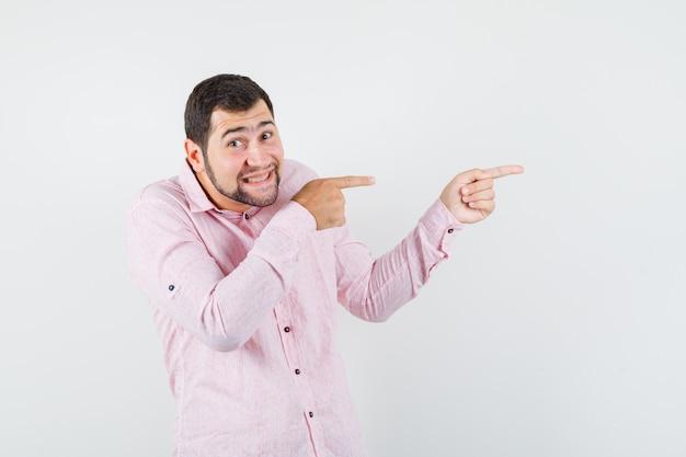 Młody Człowiek, Wskazując Na Bok W Różowej Koszuli I Wyglądający Optymistycznie Darmowe Zdjęcia