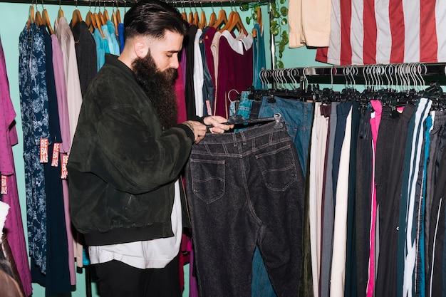 Młody człowiek wybiera cajgi wiesza na poręczu w sklepie odzieżowym Darmowe Zdjęcia