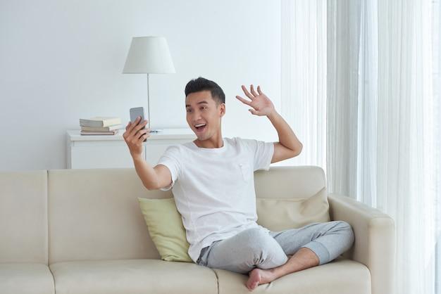 Młody człowiek, wykonując połączenie wideo, siedząc na kanapie w swoim salonie i dając gest fali powitania Darmowe Zdjęcia