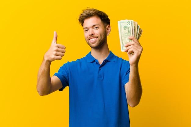 Młody człowiek z banknotami pomarańczowymi Premium Zdjęcia