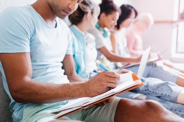 Młody Człowiek Z Brązową Skórą W Niebieskiej Koszuli, Pisząc Wykład W Notesie, Siedząc Obok Kolegów Z Uniwersytetu. Wewnątrz Portret Studentów Studiujących Razem W Bibliotece Uczelni. Darmowe Zdjęcia