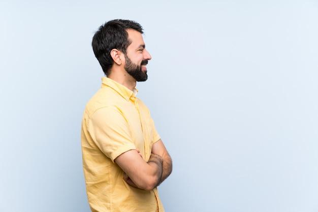 Młody człowiek z brodą na białym tle niebieski w pozycji bocznej Premium Zdjęcia