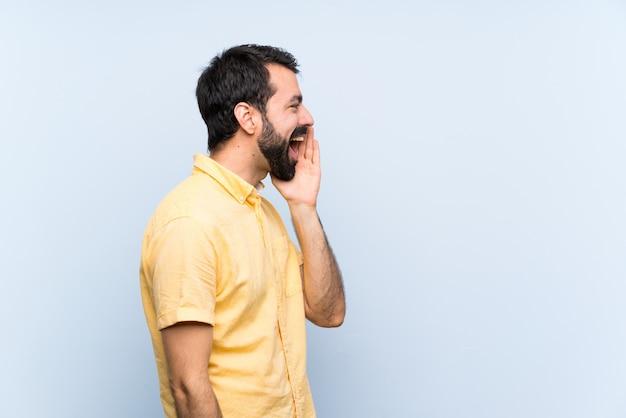 Młody człowiek z brodą na pojedyncze niebieską ścianą, krzycząc z szeroko otwartymi ustami do boku Premium Zdjęcia