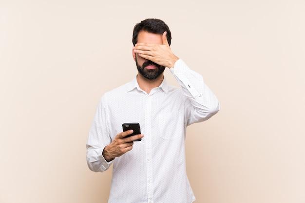 Młody człowiek z brodą trzyma mobilny nakrycie ono przygląda się rękami. nie chcę czegoś widzieć Premium Zdjęcia