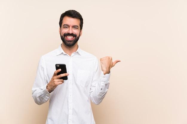 Młody człowiek z brodą trzyma telefon komórkowy wskazując na bok, aby przedstawić produkt Premium Zdjęcia
