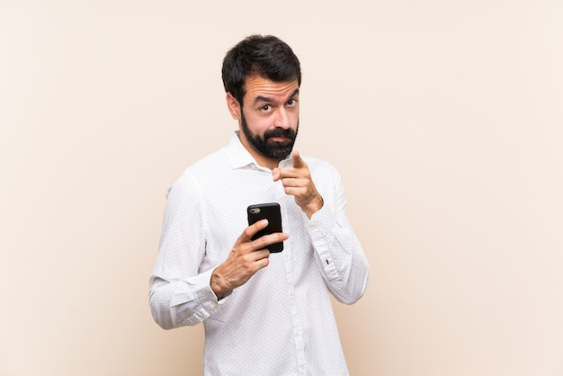 Młody człowiek z brodą, trzymając telefon udaremniony i wskazując na przód Premium Zdjęcia
