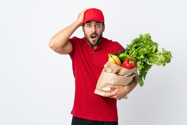 Młody Człowiek Z Brodą, Trzymając Torbę Pełną Warzyw Na Białym Tle Na Białej ścianie Z Wyrazem Twarzy Zaskoczenia Premium Zdjęcia