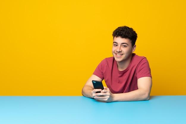 Młody człowiek z kolorową ścianą i stołem wysyła wiadomość z wiszącą ozdobą Premium Zdjęcia