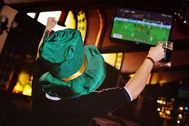 Młody Człowiek Z Kuflem Ciemnego Piwa I Zielonym Kapeluszem Z Oktoberfest Ogląda Piłkę Nożną W Barze Lub Pubie Sportowym. Premium Zdjęcia