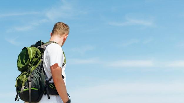 Młody człowiek z podróżnym plecakiem przeciw niebieskiego nieba tłu Darmowe Zdjęcia