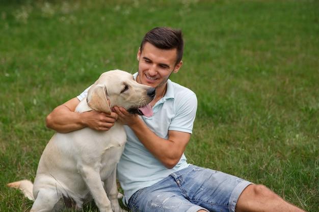 Młody Człowiek Z Szczęśliwym Labradorem W Parku Premium Zdjęcia