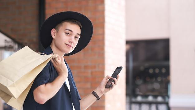 Młody człowiek z torby na zakupy korzysta z telefonu komórkowego podczas robienia zakupów Premium Zdjęcia